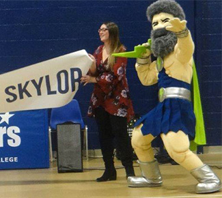 The Skylander mascot stands next to a student holding the banner.