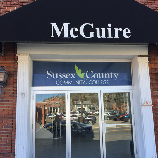 Images is the front of a brick building with the words McGuire on a black awning.