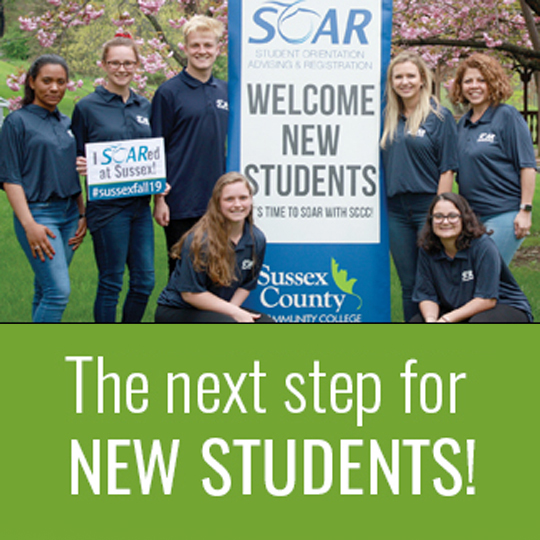 Student SOAR leaders in blue shirts near the SOAR signage