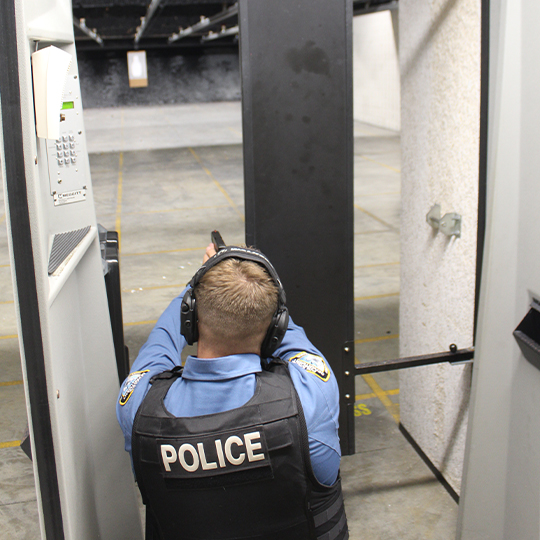 Image of a police officer in uniform firing a gun at the gun range.